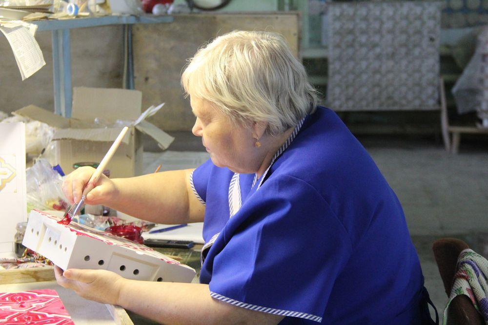 Художница вручную расписывает иконостас при помощи старого пера с деревянной ручкой